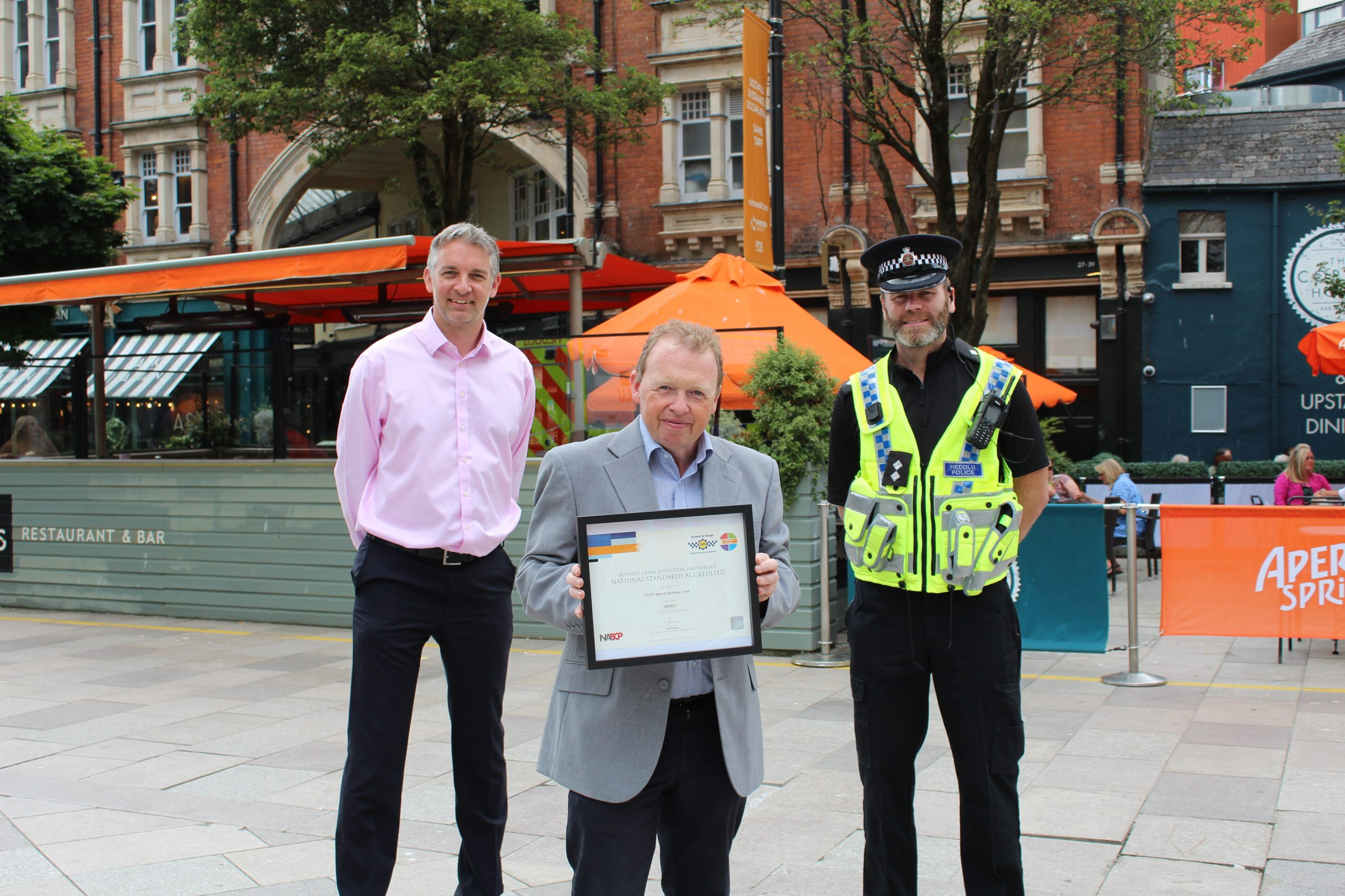 three men standing in Cardiff city centre with one man holding the reaccreditation certificate